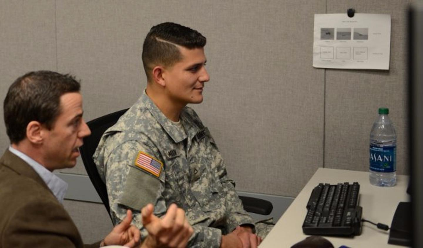 Anthony Ries instructs Pfc. Kenneth Blandon on how to play a computer game that uses eye-tracking technology