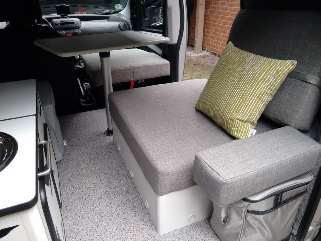 Flexcamper has created a functional, little interior for one person, complete with table, convertible seat/bed and kitchen equipment – the cushion on top of the fridge looks like a comfy armrest