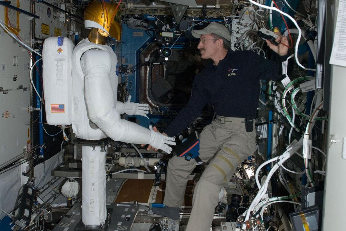 Astronaut Dan Burbank and NASA's Robonaut 2 shake hands on the ISS (Photo: NASA)