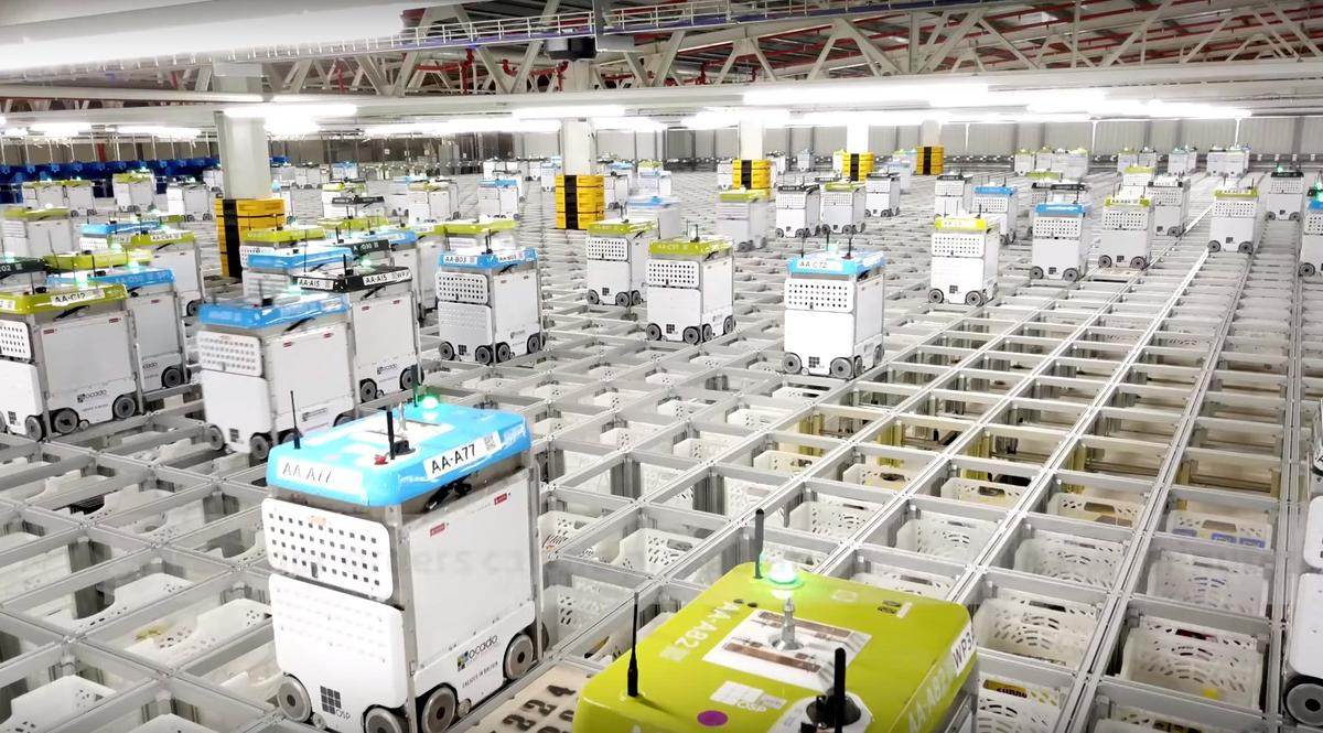 Ocado's Andover CFC features a three story high aluminum grid containing crates that are picked up by robots and carried over to collection points