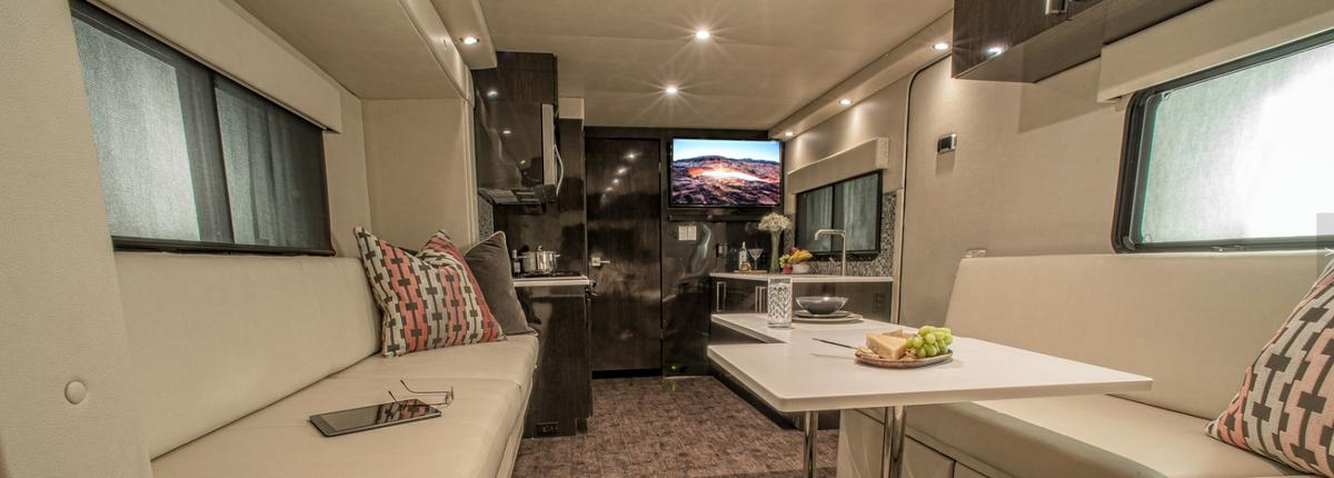 The interior includes modular tables, a kitchen and a rear entertainment lounge