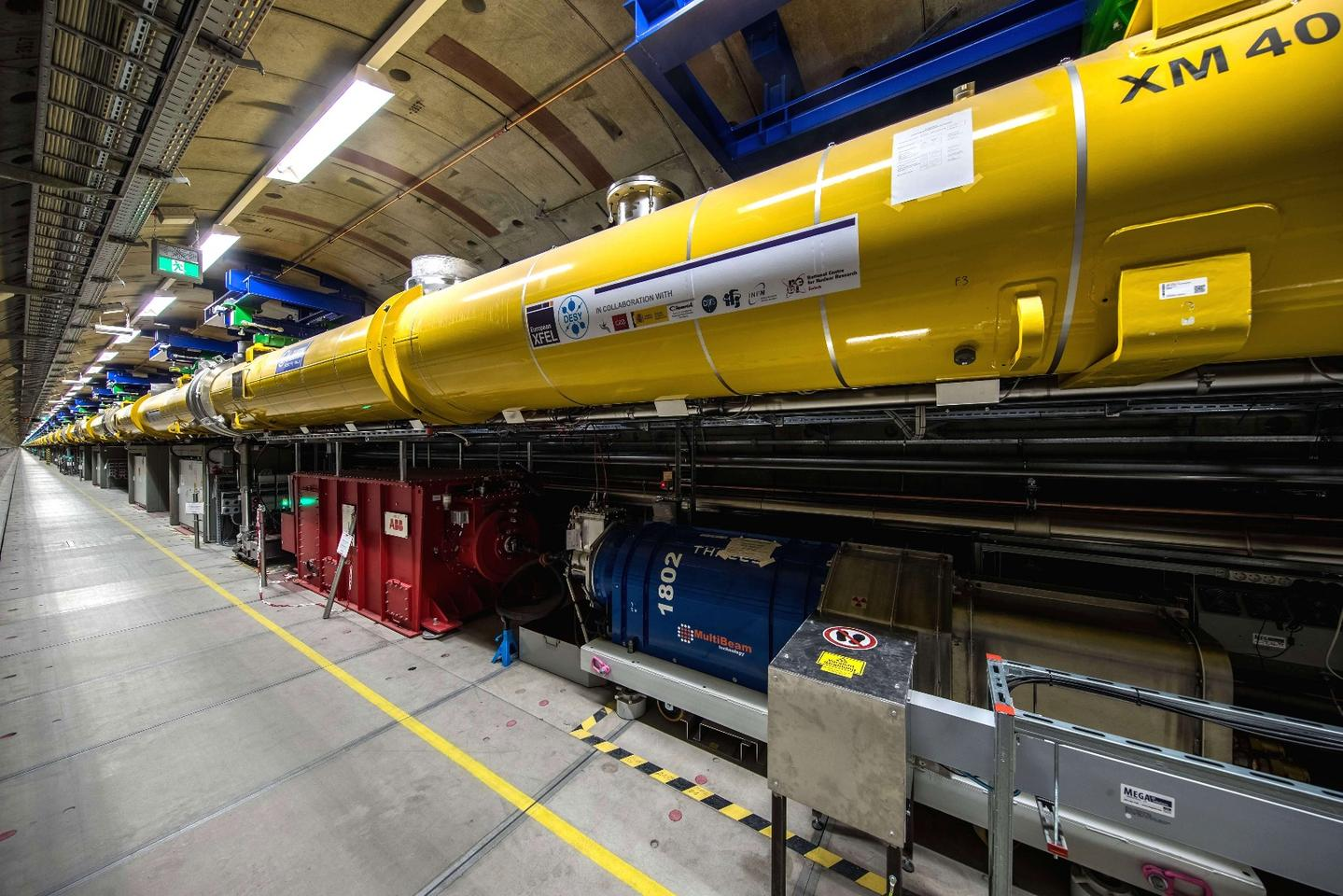View into the 2.1-km long accelerator tunnel of theEuropean XFEL with the yellow superconducting accelerator modules hanging from the ceiling