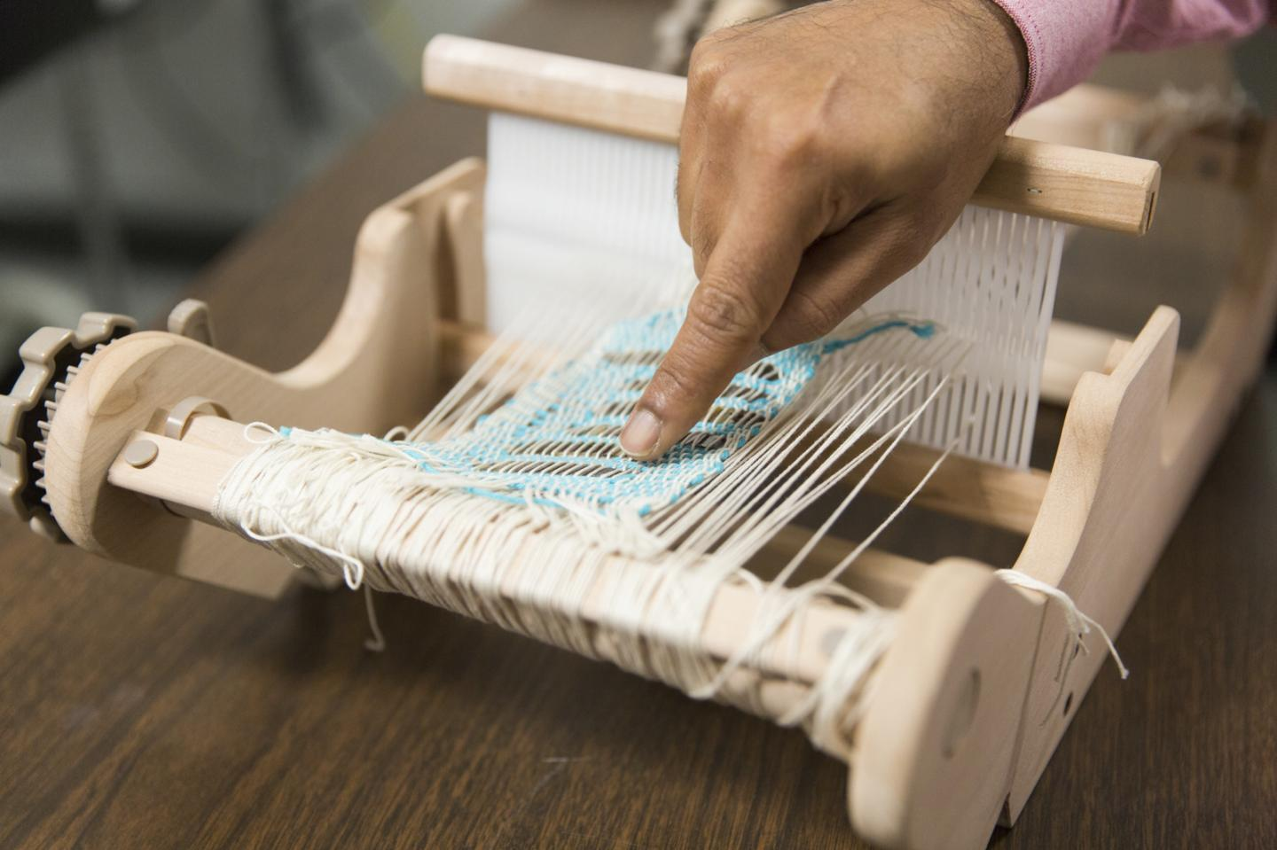 The researchers had to learn to use a loom to weave their power-storing fabric