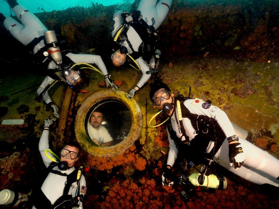 The NEEMO16 Crew with Astronaut Dottie, Astronaut Kimiya, Dr. Steve, Astronaut Tim, and James in Aquarius porthole (Photo: NASA)