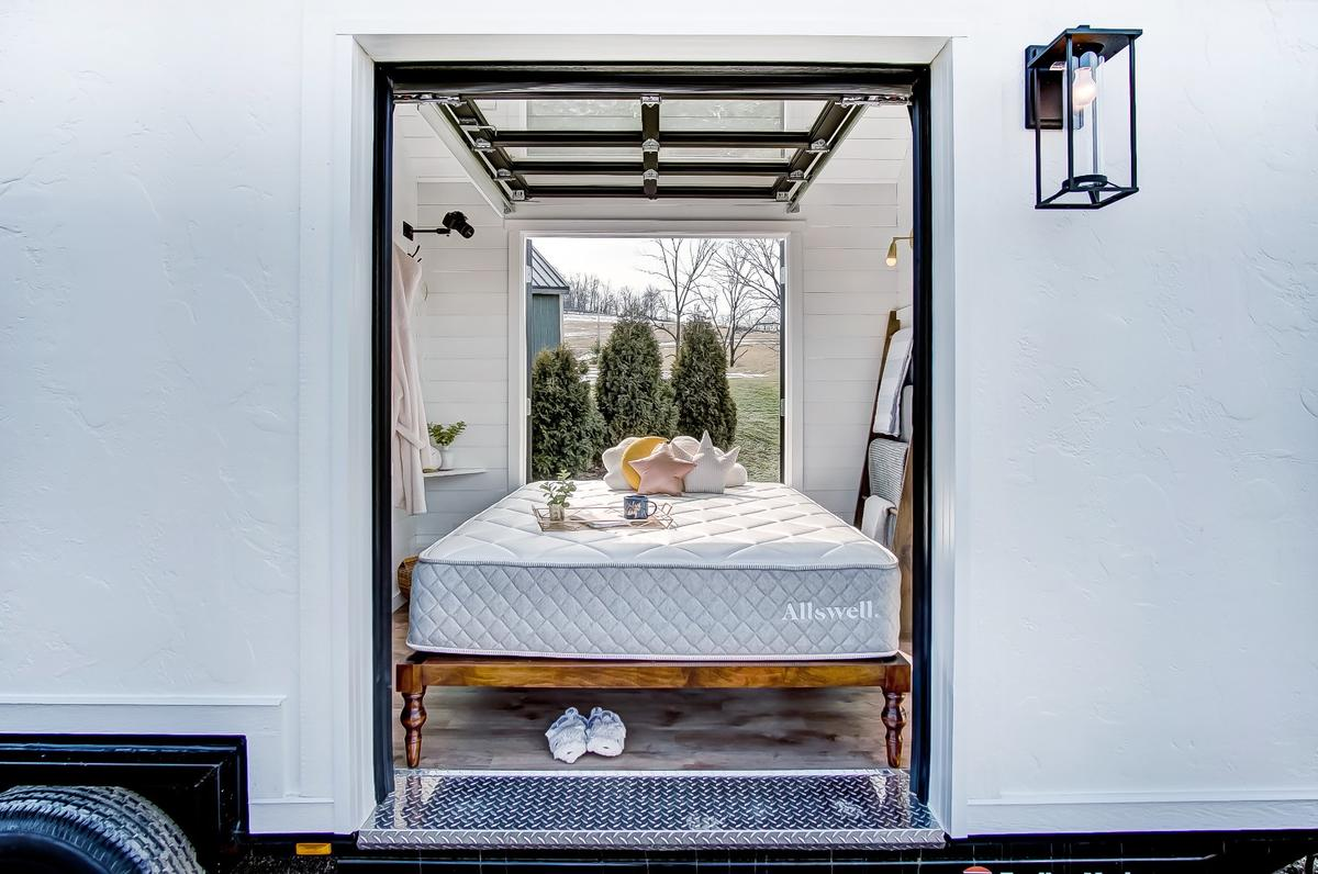 The Allswell Tiny Home's bedroom opens to the outside with a garage-style door and French doors