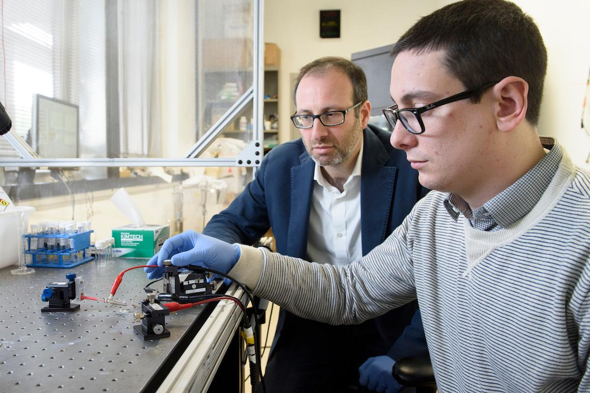 Alberto Salleo (left) and Scott Keene, two of the researchers on the project, test the artificial synapse