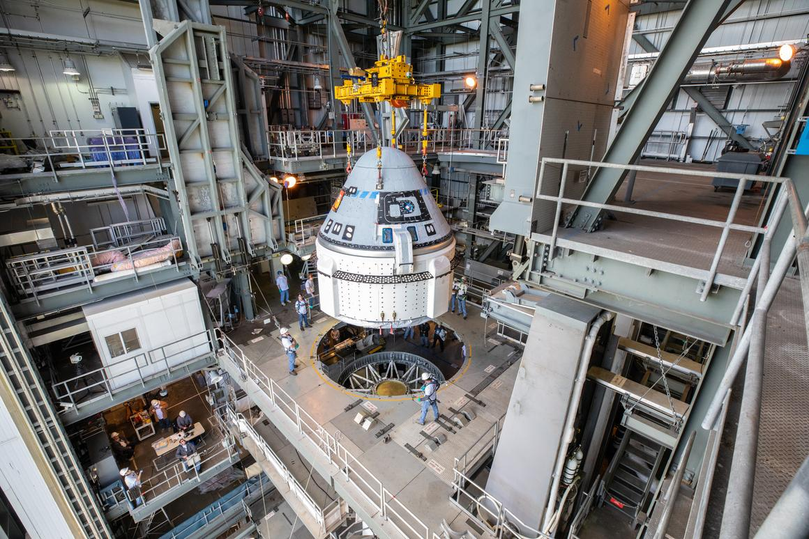 The Boeing CST-100 Starliner spacecraft is guided into position above a United Launch Alliance Atlas V rocket at the Vertical Integration Facility at Space Launch Complex 41 at Florida's Cape Canaveral Air Force Station