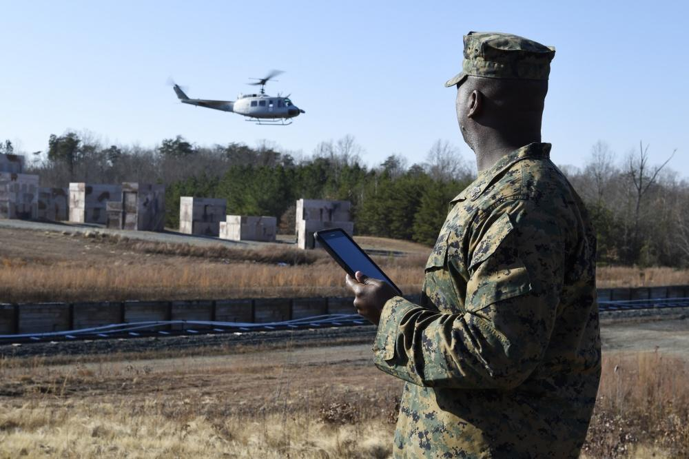 Sgt. Dionte Jones watches as a UH-1 Huey equipped with AACUS autonomy kit departs the landing zone following a resupply mission he requested using a handheld tablet