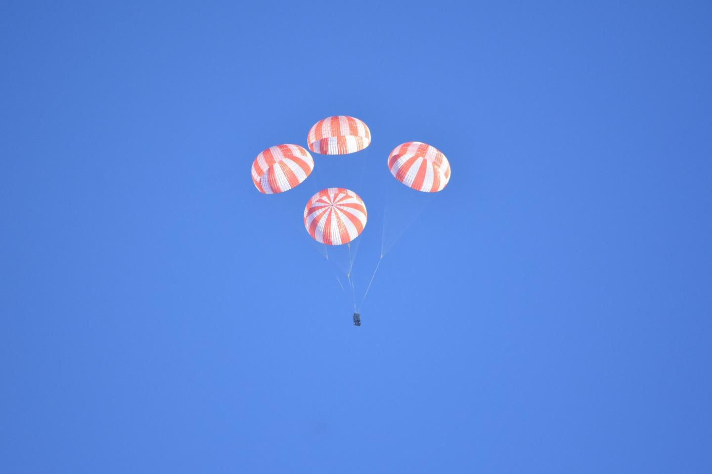 SpaceX's mass simulator descending under four deployed main stage parachutes