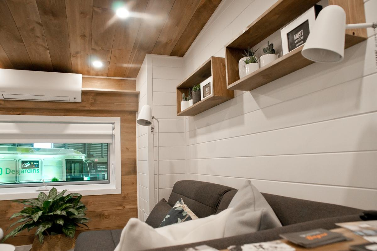 The Noyer's living room includes shelving and a small air-conditioning unit that helps keep the interior a comfortable temperature