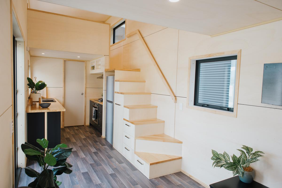 The Home Haven's main bedroom is reached by storage-integrated staircase