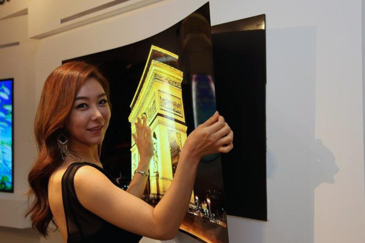 "A model peels LG Display's ""wallpaper OLED"" panel from its magnetic mount"