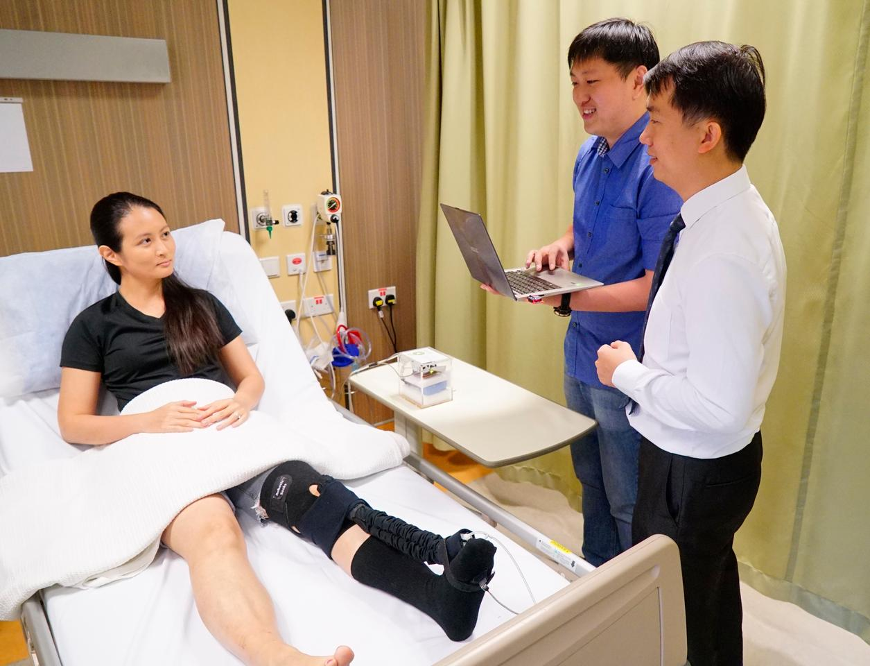 NUS researchers (from right to left) Assistant Professor Raye Yeow, Mr Low Fanzhe and Dr Liu Yuchun demonstrating the novel bio-inspired robotic sock (Photo: National University of Singapore)
