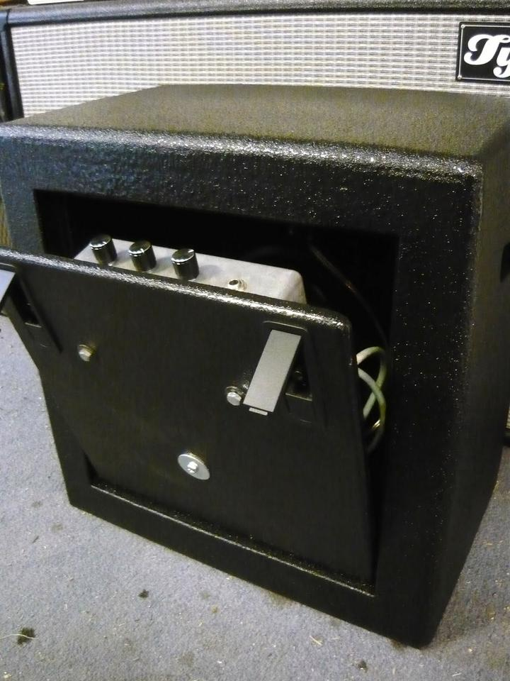 The back panel pulls down to reveal the 50W solid state amp inside the foam-encased combo FAMP