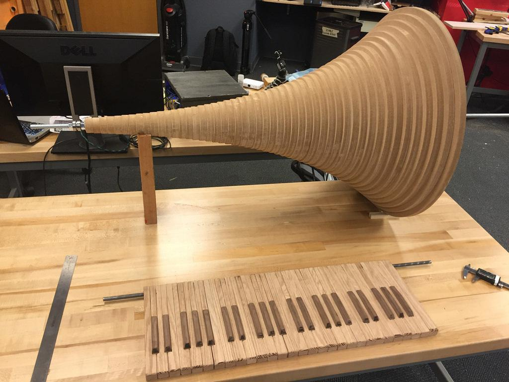 "The cone is made from CNC-machined MDF disks, while the keyboard is cut from oak (with the ""black"" keys being topped by walnut)"
