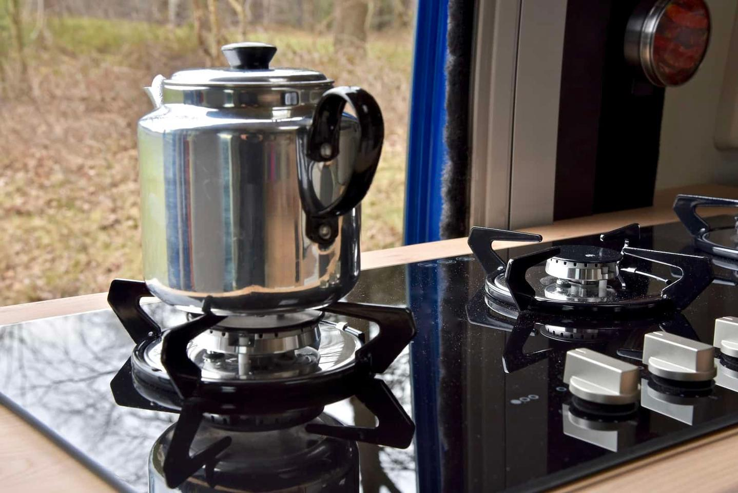 A kettle on the triple-burner stove