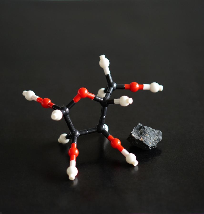 A molecular model of ribose, a bio-essential sugar, next to the Murchison meteorite in which it was found