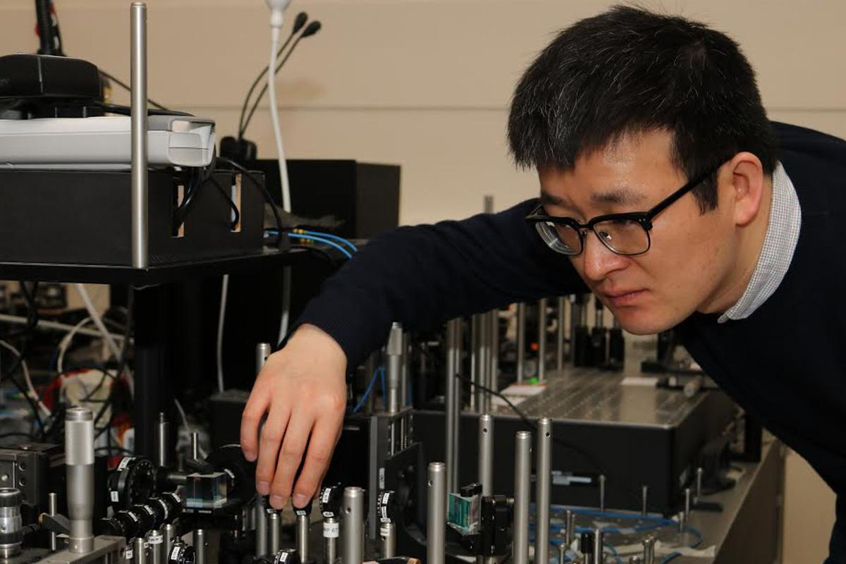Bristol PhD student Xiaogang Qiang and the primitive photonic quantum processor he designed with UWA researchers to simulate quantum walks