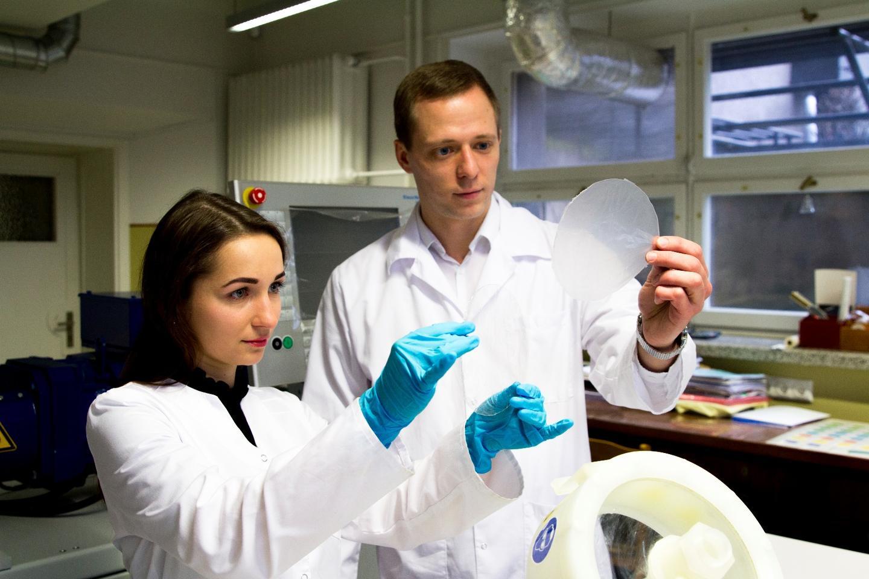 PhD student Vesta Navikaitė-Snipaitienė (left) and Paulius Pavelas Danilovas examine the material