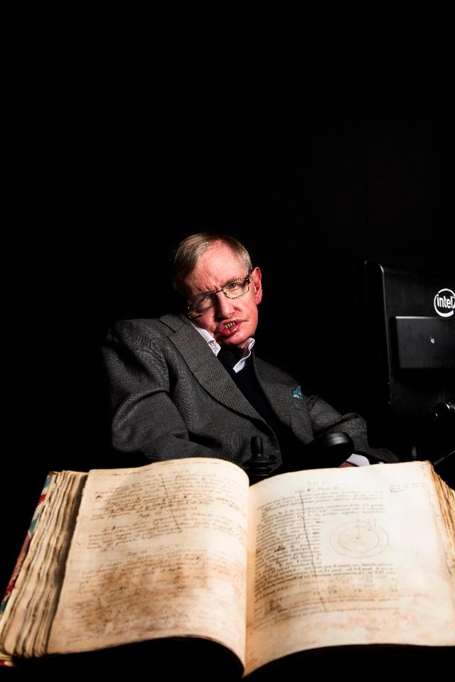 Stephen Hawking pictured with Isaac Newton's own annotated copy of Principia Mathematica