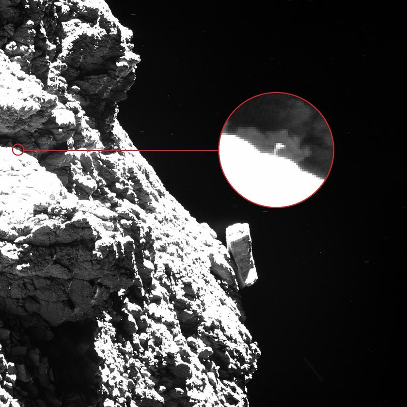 """In this Rosetta image, one of the Philae lander's """"feet"""" can be seen protruding from behind an obscuring boulder to the upper left of the shot, appearing as a thin vertical line with a broad top"""