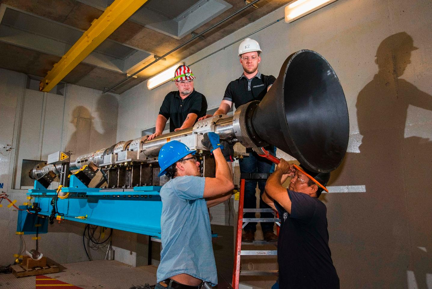 Sandia engineers attach a resonant cone to a modified Hopkinson bar known as a resonant beam, in preparation for an alternative pyroshock test