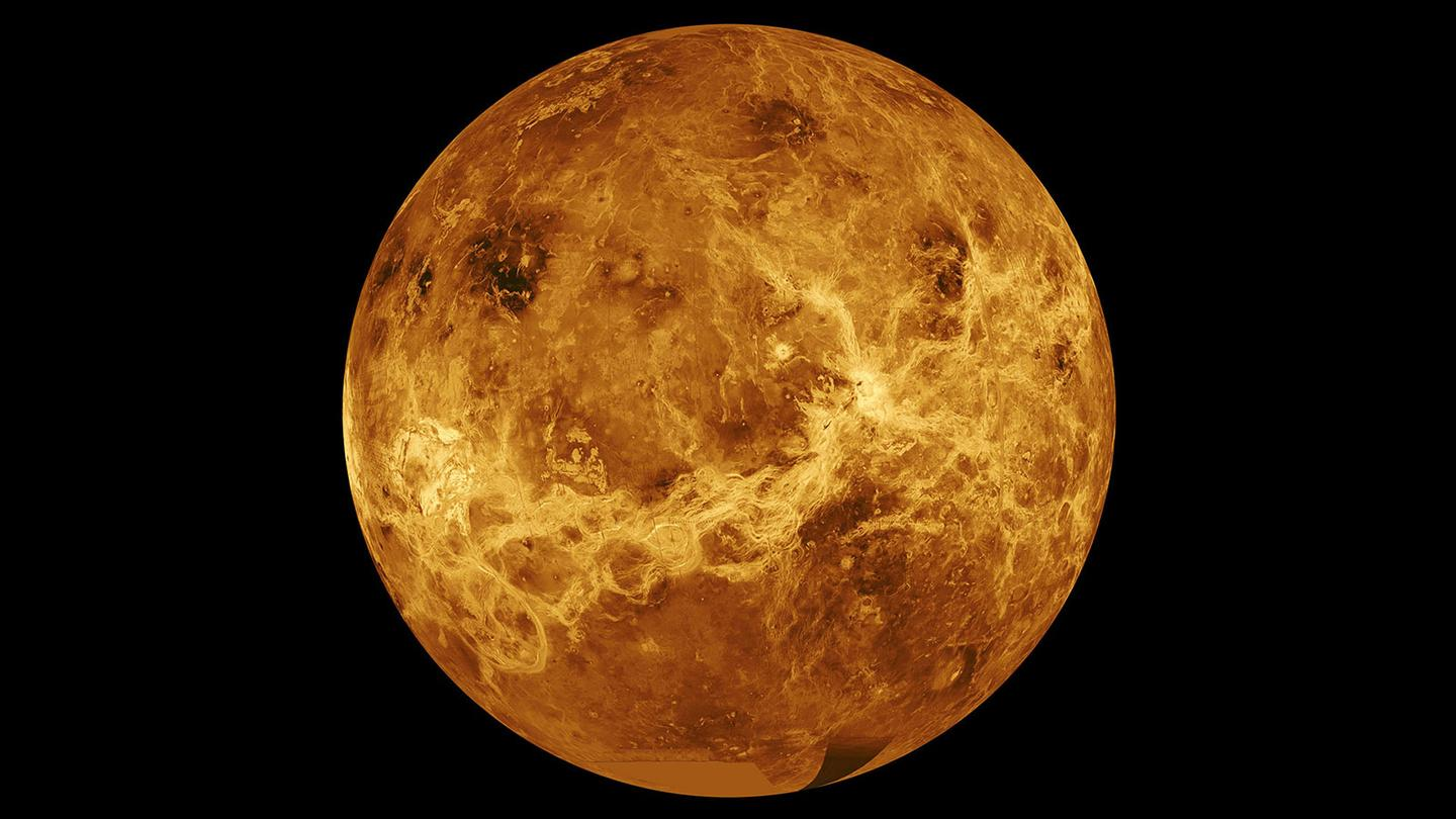 A composite image peering beneath the Venusian atmosphere to the surface below.