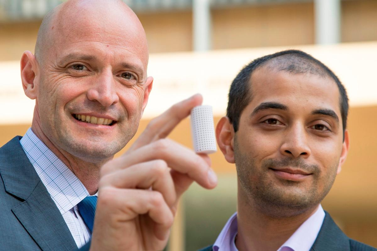 J.R. DeShazo (left) and Gaurav Sant show off a sample of the new building material they have created to replace conventional concrete