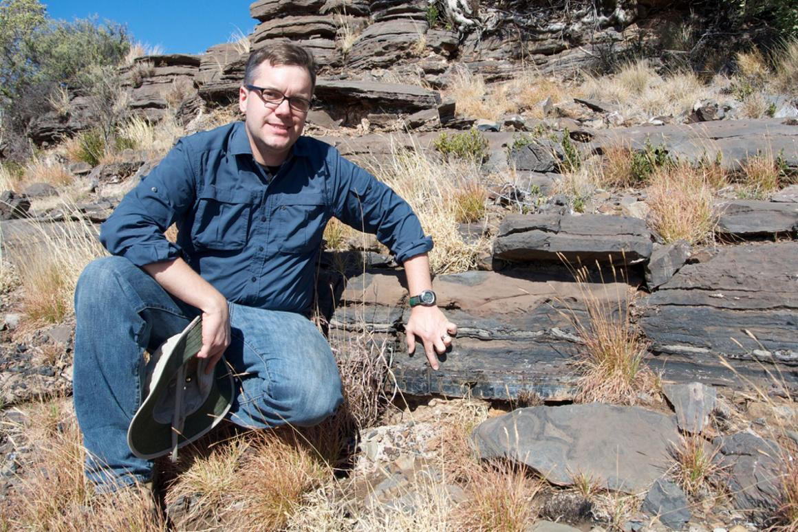 ProfessorAndrew Czaja shows the layer of rock where the bacteria were discovered