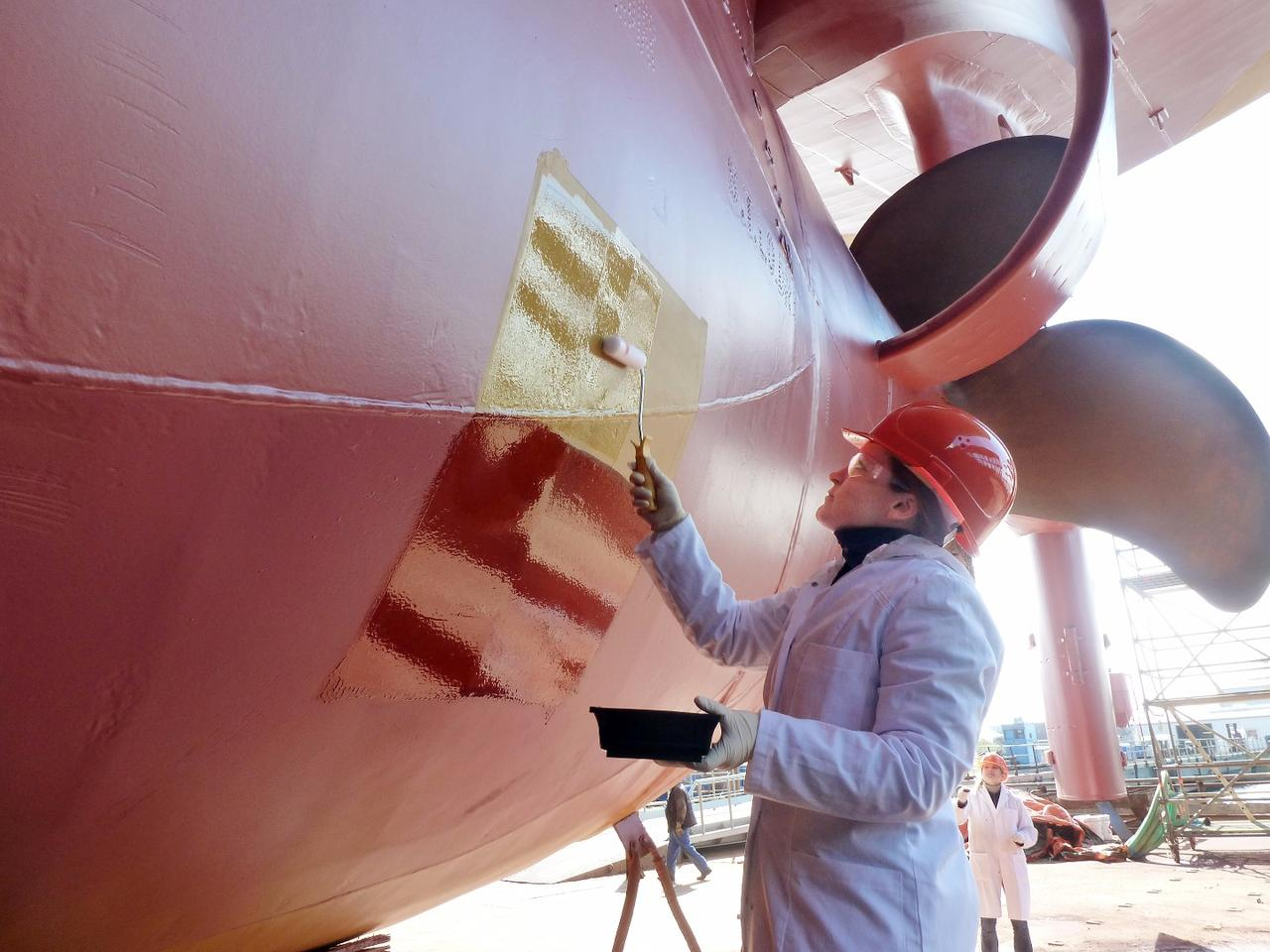 """Dr. Martina Baum applies a test patch of the paint to the ship """"African Forest"""""""