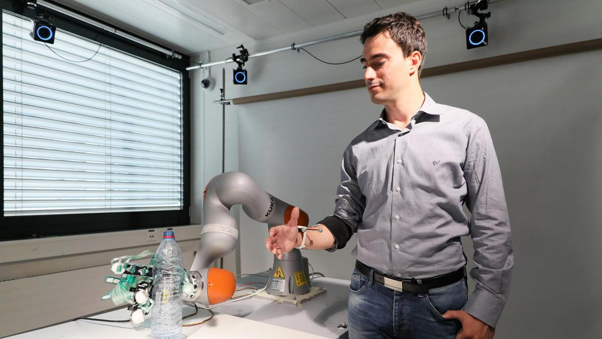 Researcher Artoni Fiorenzo demonstrates the shared control system, using a robotic arm