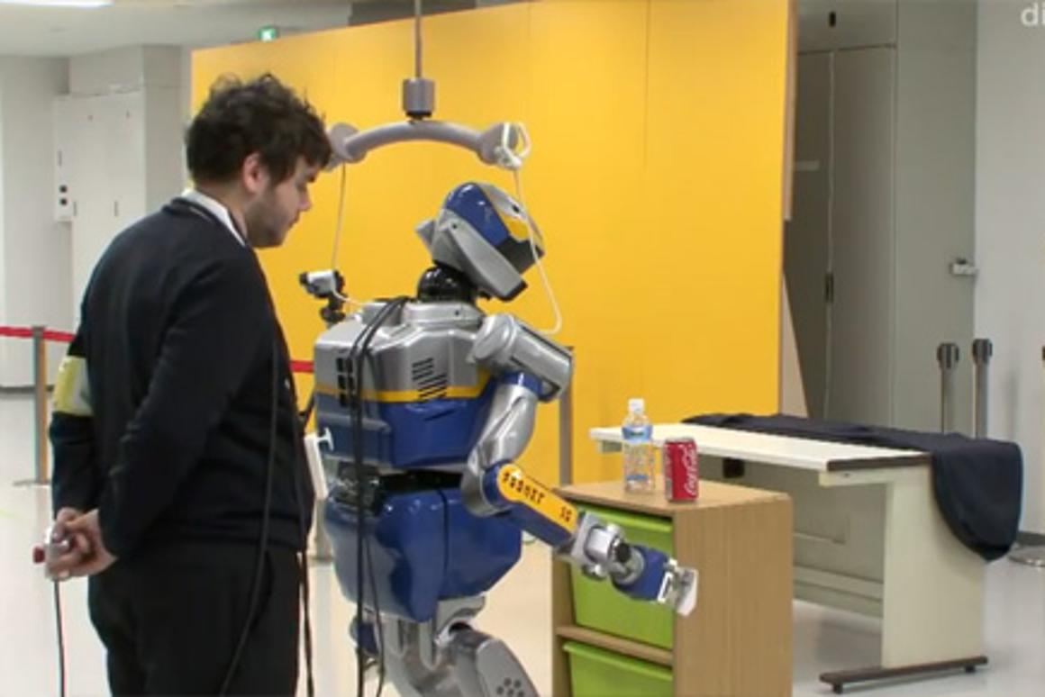 A researcher minds the robot's balance as it is commanded to pick up a canned drink by an operator (off camera)