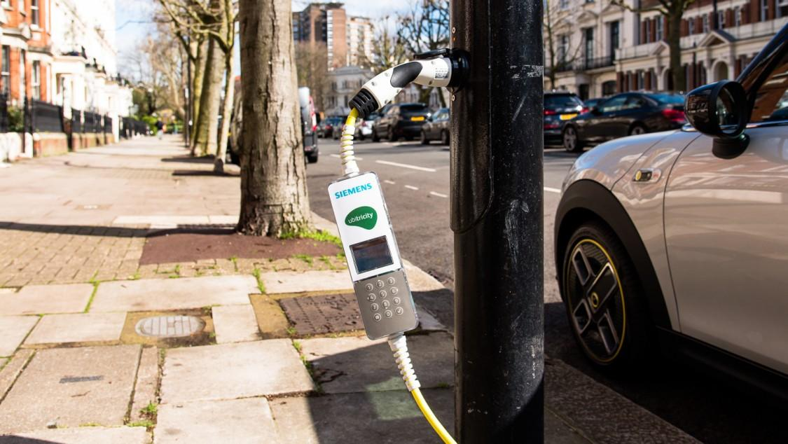A cable featuring a smart meter is plugged into the electric vehicle and streetlamp for overnight charging