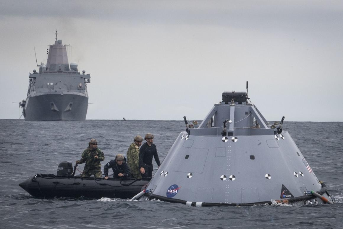 US Navy divers attach tow lines to a dummy Orion capsule
