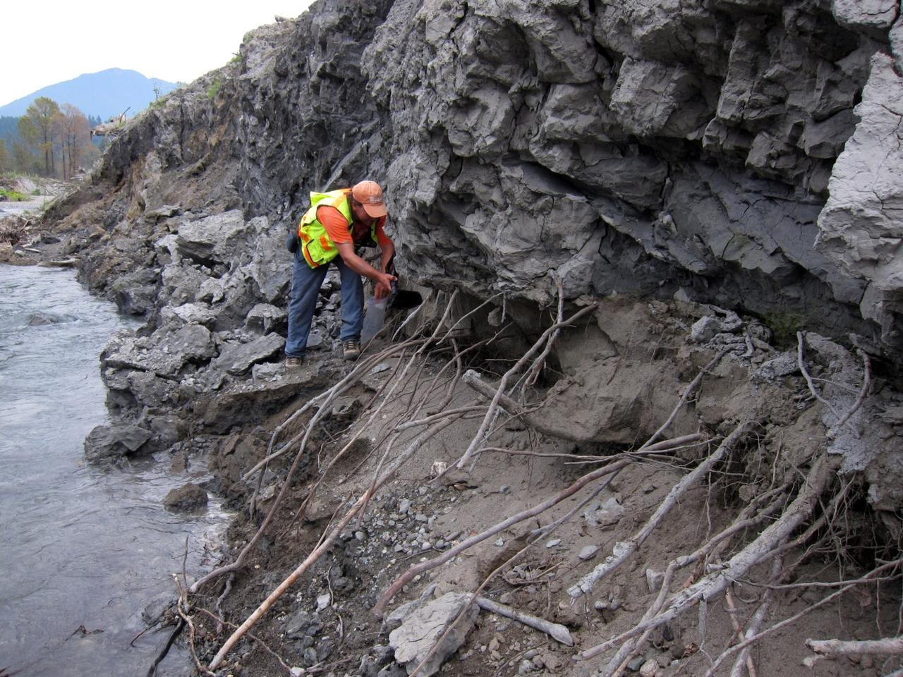 US Geological Survey civil engineer Brian Collins examines gray clay deposits overlying the brown sand that forms the underlying alluvial river valley
