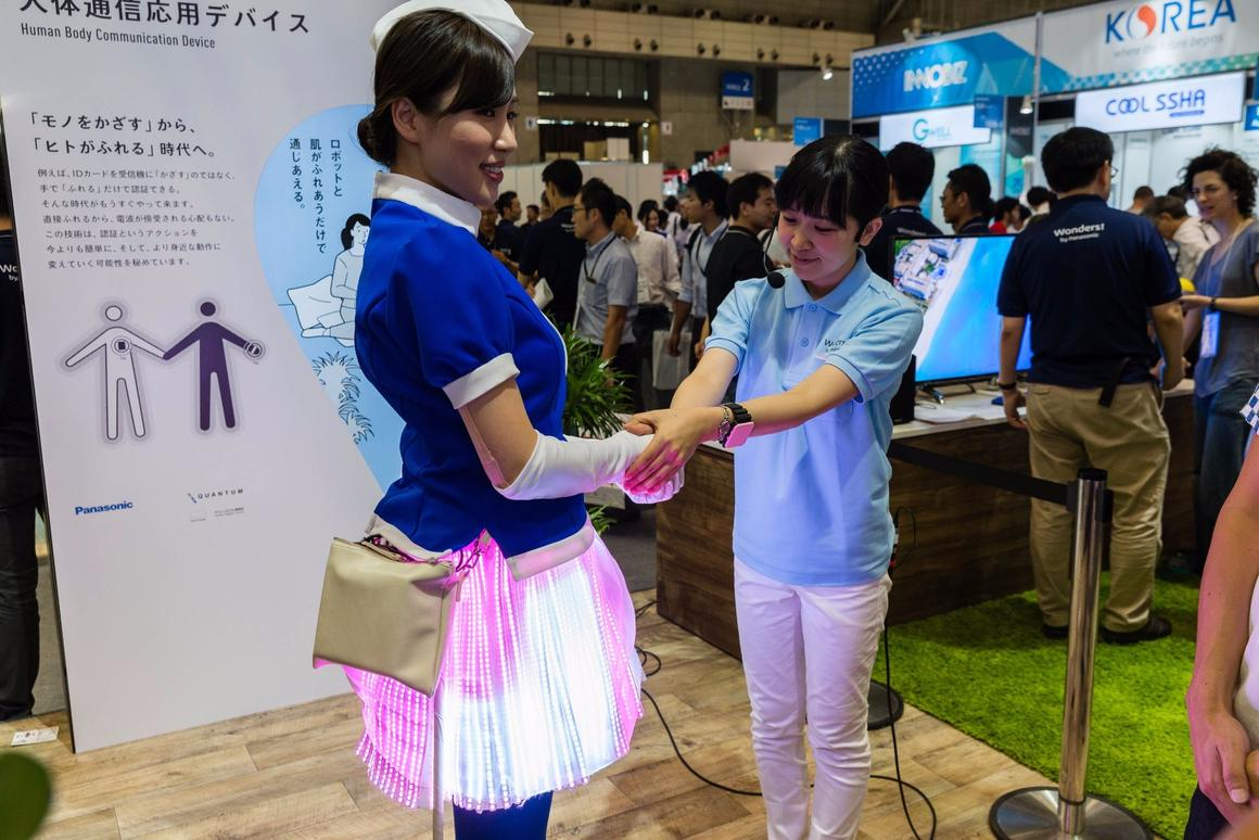 The LEDs under one staff member's skirt change to match the color of a bracelet worn by another when they shake hands
