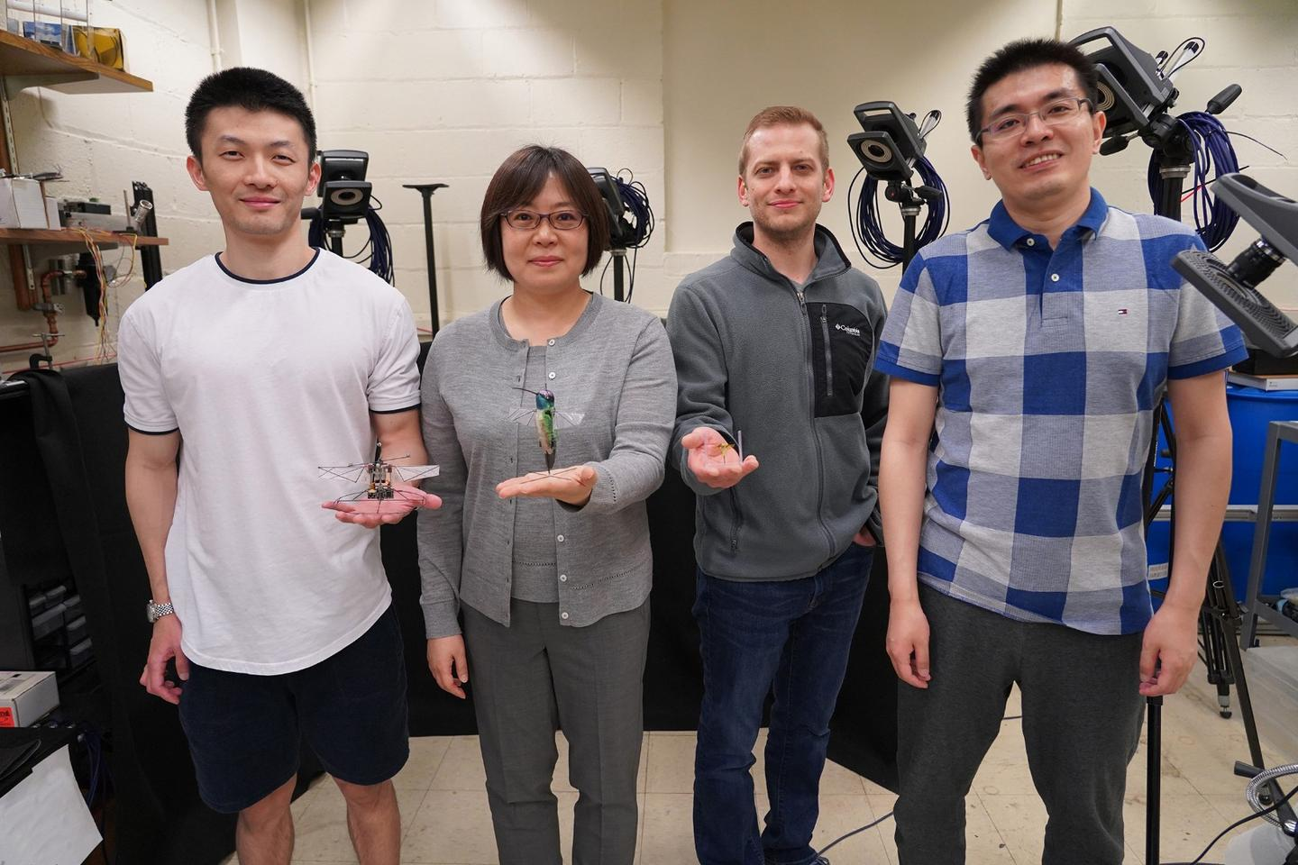 The researchers on the team (from left: Fan Fei, Xinyan Deng, Jesse Roll and Zhan Tu), with the robotic hummingbird and insects