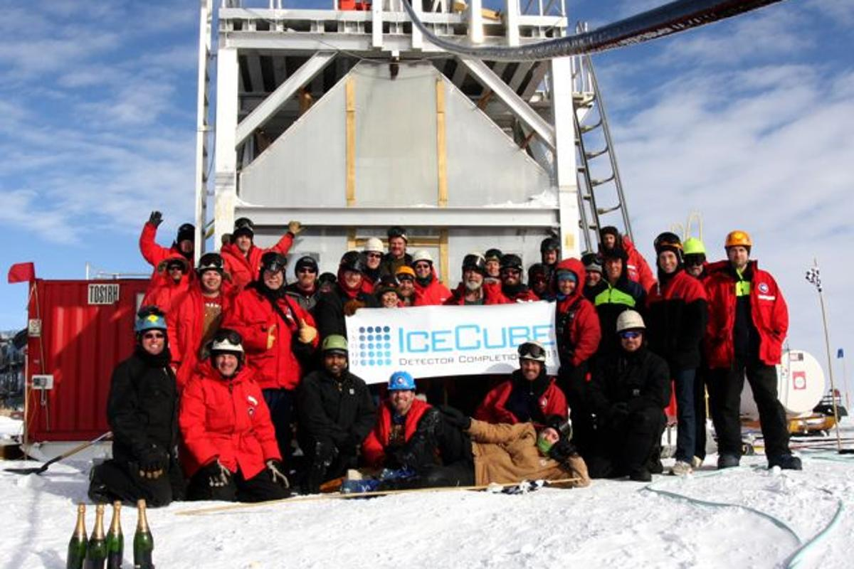The IceCube team poses in front of the deployment tower following completion of the IceCube Neutrino Detector