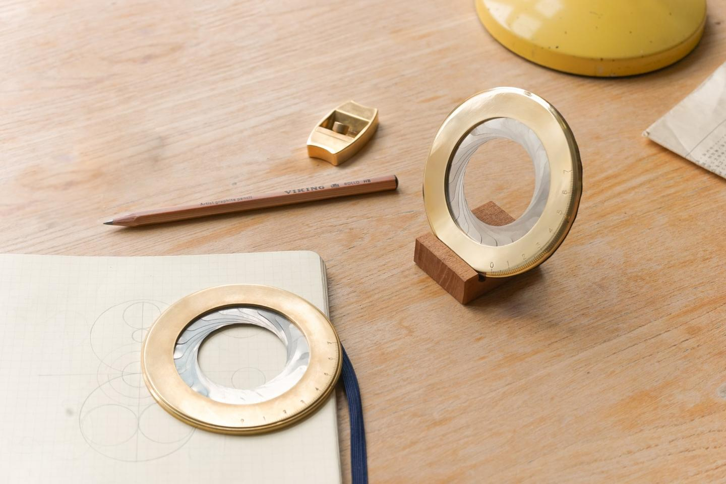 The Iris, shown with its wooden base, alongside Makers Cabinet's first Kickstarter project, theHøvel