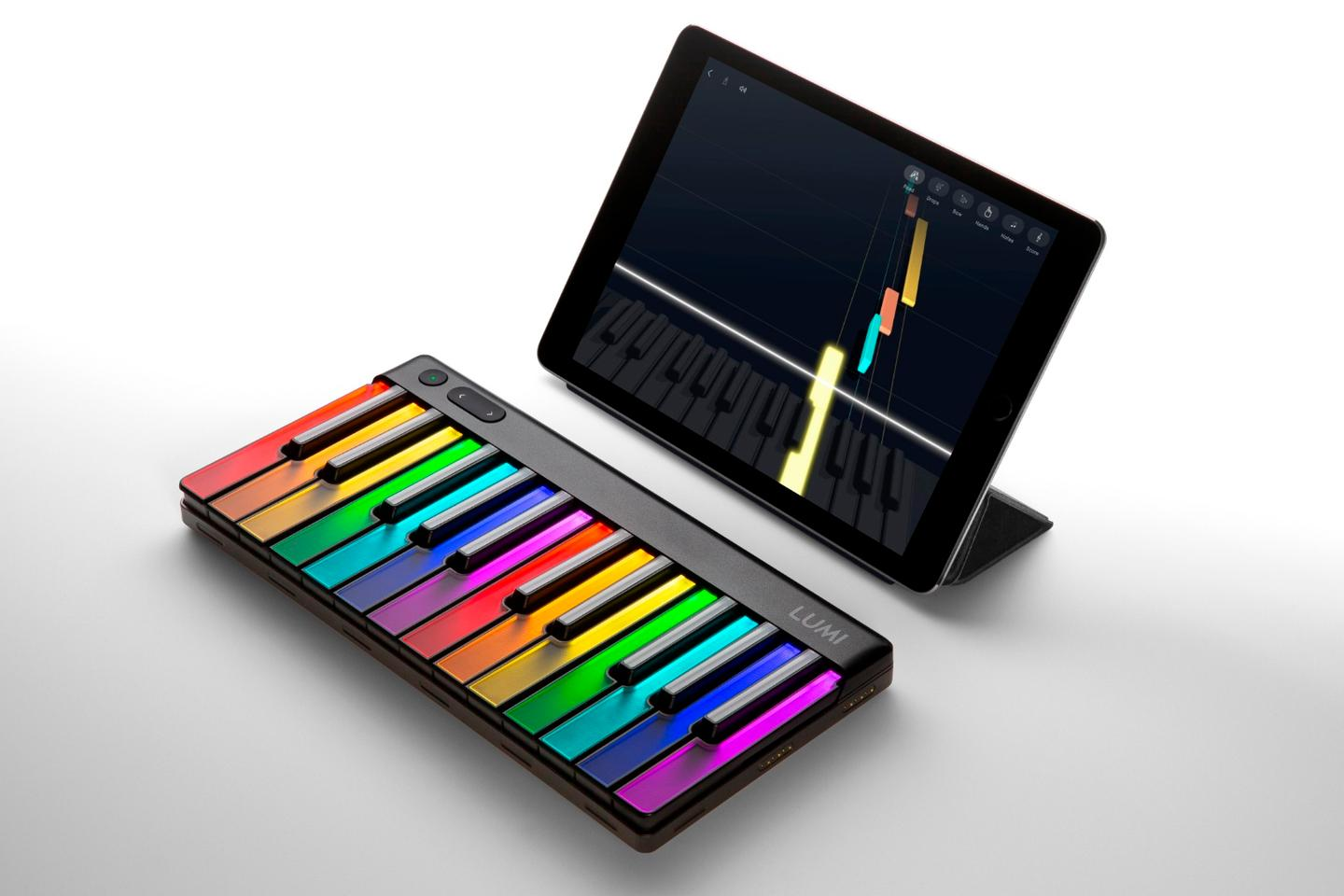 Tumbling blocks on a tablet running the Lumi app show the student where and when to press down the illuminated key on the Lumi Keys