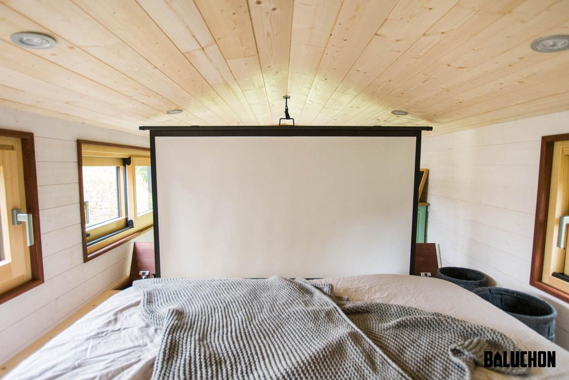 Tiny house Le Château Ambulant's bedroom, shown with the projector screen in place
