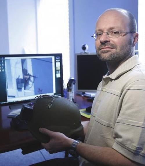 Akos Ledeczi holds a kevlar helmet with the microphones and network node attached that can turn the helmet into an accurate shooter location systemPhoto credit Steve Green, Vanderbilt University
