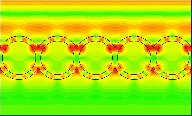 This image from a computer simulation shows how waves of light (in red/orange, traveling from the top of image to the bottom) strike a layer of nanoshells and how the light resonates within the shell structure (in red)