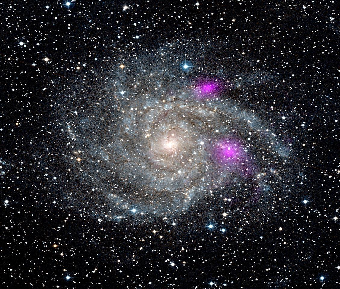 Black holes blaze magenta in this NuStar photo of spiral galaxy IC342 (Photo: NASA)