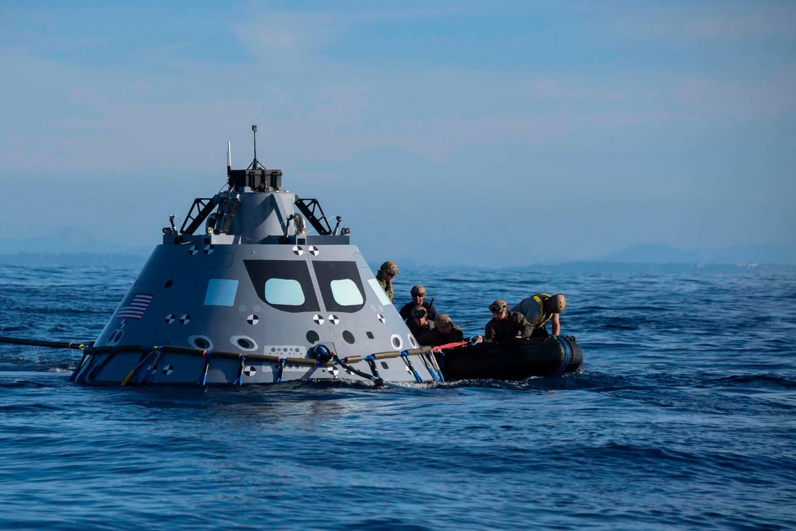 Navy divers from Explosive Ordnance Disposal Mobile Unit (EODMU) 3 attach an inflatable ring to NASA's Orion test vehicle