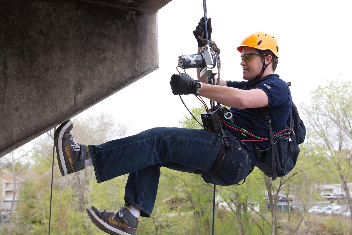 Engineering student Brady Morton uses the winch device to ascend a tower