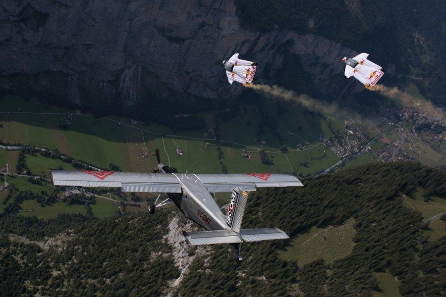 Wingsuit flyers try to catch up with a plane in mid-air