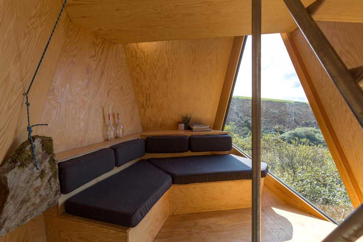 Each cabin accommodates up to two guests and features a cozy lounge with log fire and large triangular window overlooking the serene landscape