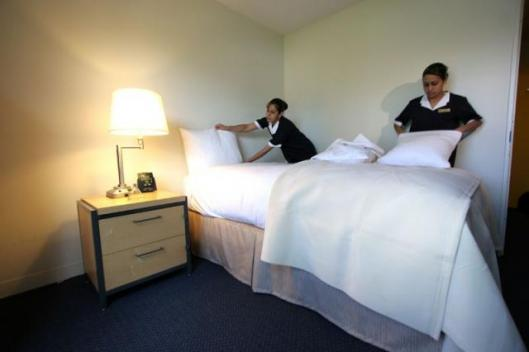 Two members of the Hilton Hotels housekeeping staff help to create Apolo Anton Ohno's Competitive Advantage dorm room, which was the first of 160 to be scientifically designed and made over by the sponsor to increase alertness and response time for athlet