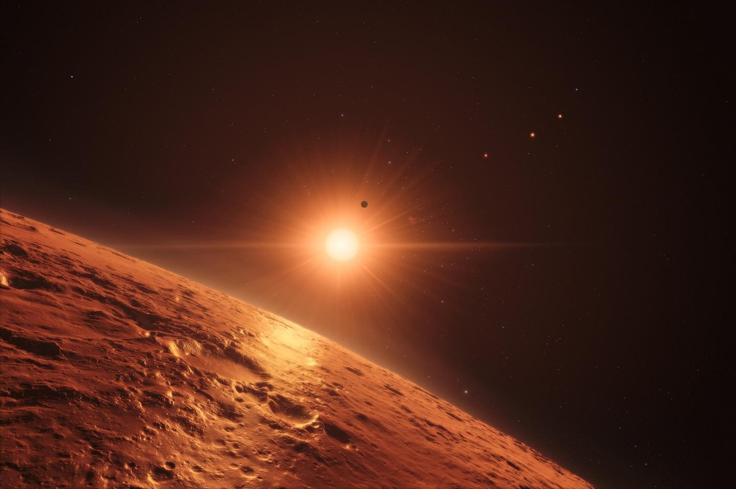 This artist's impression shows the view just above the surface of one of the middle planets in the TRAPPIST-1 system, with the glare of the host star illuminating the rocky surface